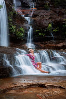 Exhilaration in mountain waterfall, female sitting in flowing cascades