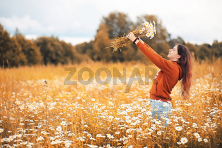 Beautiful girl collects daisies in autumn