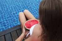 Woman with watermelon poolside