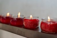 Four red candles in glass cups
