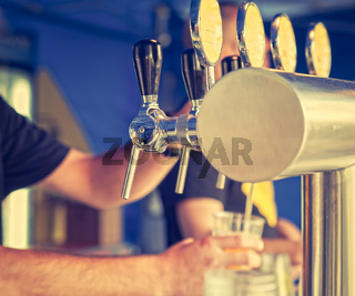 Draught draft beer taps in a bar . Vintage look