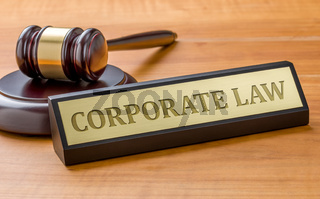 A gavel and a name plate with the engraving Corporate law