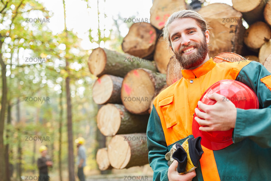 Junger lächelnder Waldarbeiter in Schutzkleidung
