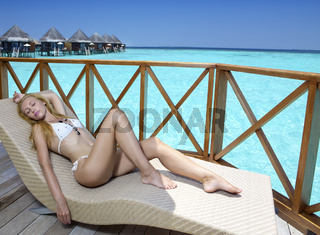 beautiful woman in a bikini bathing suit has a rest in sunbed on a wooden terrace and the sea with houses over water on a background