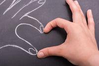 Hands forming a heart on blackboard