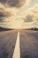 empty runway, straight highway road with dramatic sky  -