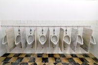 Mens room with white porcelain urinals in a row