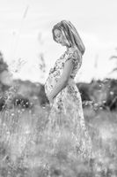 Beautiful pregnant woman in white summer dress in meadow full of yellow blooming flovers.