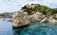 Huge stones rcky coast of Cala en Cranc of Mallorca, picturesque nature turquoise Mediterranean waters bay, hillside house summer villa, cloudy sky. Balearic Islands, Palma de Mallorca, Spain