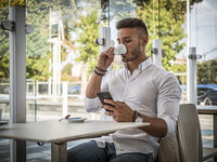 Attractive Young Man Drinking Espresso Coffee at Bar