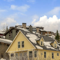 Square Houses on snow covered ground against blue sky with puffy clouds in winter