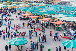 MARRAKESH, MAROCCO - FEBURARY 25, 2018: aerial view of people walking on Jemaa EL Fnaa main city square. Crowd at warm sunset color tones at market place in Marrakesh's medina quarter.