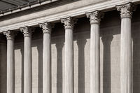 Vintage Old Justice Courthouse Column. Neoclassical colonnade with corinthian columns as part of a public building resembling a Greek or Roman temple