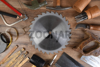 High angle closeup of a large group of tools arranged around a round table saw blade