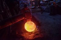 blacksmith workers using mechanical hammer at workshop