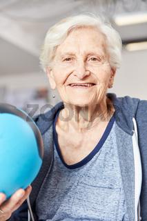 Glückliche Senior Frau mit Ball in der Ergotherapie
