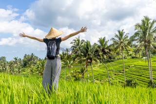 Relaxed fashionable female traveler wearing small backpack and traditional asian paddy hat, arms rised to sky, enjoying pure nature at beautiful green rice fields and terraces on Bali island