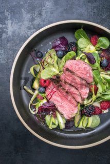 Traditional barbecue aged sliced fillet steak with lettuce and fruits as top view on a plate with copy space