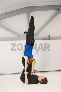 Theme is sports and acreage. A young Caucasian male and female couple practicing acrobatic yoga in a white gym on mats. a man lies on his back and holds a woman on extended arms. Pose HAND-TO-HAND