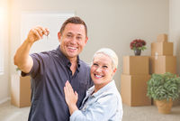 Happy Couple With New House Keys Inside Empty Room with Boxes
