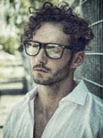 One handsome man in city setting wearing glasses
