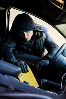 Taschendieb beim Stehlen von Handtasche aus Auto