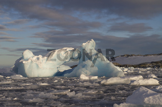 small iceberg in Antarctic waters clogged with ice against a rocky shore