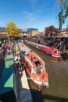 London, England UK - May 14, 2019: Boat navigating to the Regent's Canal with people around in Camden Lock or Camden Town in London, England, United Kingdom.