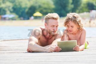 Vater und Sohn mit Tablet Computer in der Sonne