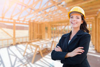 Smiling Female Contractor In Hard Hat At Construction Site