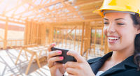 Smiling Female Contractor In Hard Hat Using Smart Phone At Construction Site