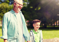 grandfather and grandson walking at summer park