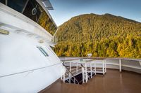 Forward outside upper deck below cruise ship bridge passing by Alaska Inside Passage natural scenery