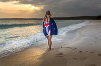 Woman draped in Australiabn Flag on a beach in early morning
