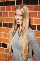 teenage girl leaning against brick wall