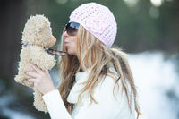 Girl blowing kisses to scruffy teddy bear