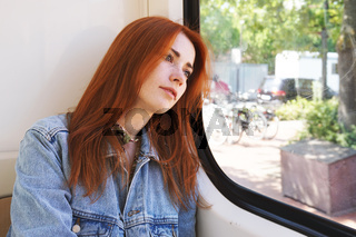 young woman sitting in tram or streetcar looking out of the window