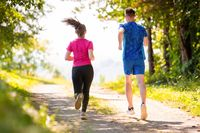 young couple jogging on sunny day at nature