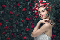 Summer woman portrait inspired by nature lifestyle. Beauty spring girl with blooming flowers wreath hairstyle on her head.