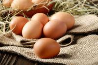 Fresh brown organic chicken eggs on wooden table and hemp burlap