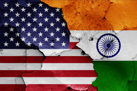 flags of USA and India painted on cracked wall