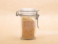 Weizenkeime in Glas mit Deckel auf braunem Hintergrund - Wheat germs in closed jar on brown background