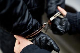Hände mit Handschellen hinter Rücken gefesselt