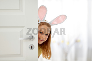 happy girl with easter bunny ears peeking out door