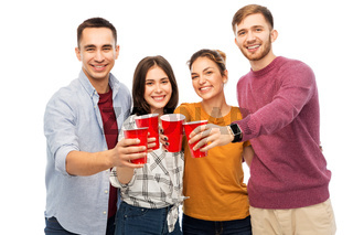 group of smiling friends with drinks in party cups