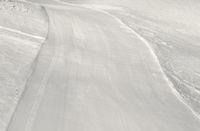 Prepared snowy ski slope after snow grooming machine