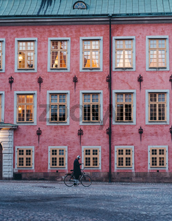 Man walking by with his bike and checking phone with old building facade in the background