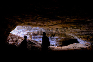 Two unrecognizable tourists at the entrance of Gruta Da Lapa Doce, cave in Iraquara, Chapada Diamantina, Bahia, Brazil