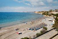 Torrevieja, Spain - June 25, 2019: Above top view holidaymakers enjoy summer vacation holidays on seaside near Mediterranean Sea of Cabo Roig sandy beach coast, Torrevieja resort, Costa Blanca, Spain