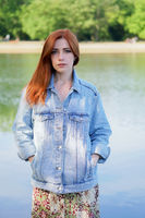 authentic young woman wearing denim jacket over summer dress standing by lake